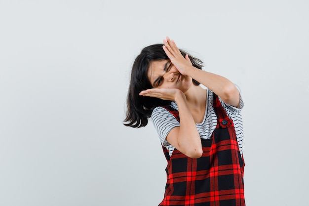 Preteen dziewczyna trzymająca się za ręce na nadętych policzkach w t-shircie
