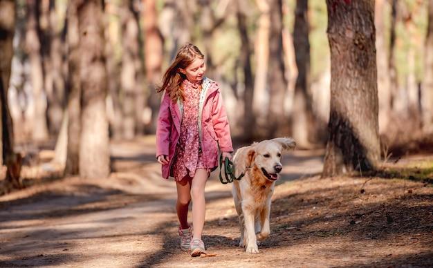 Preteen dziewczyna ubrana w różowy płaszcz ze złotym psem retrieverem spacerująca po lesie