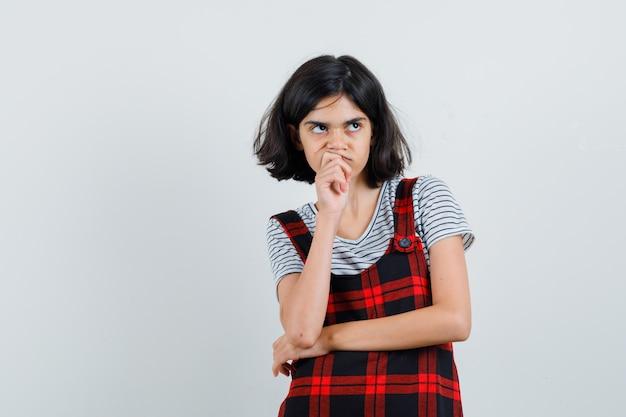 Preteen dziewczyna w koszulce, kombinezonie myśli coś i wygląda na zamyśloną