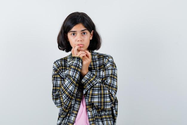 Preteen dziewczyna w koszuli, kurtce, patrząc na kamery i patrząc na spokój, widok z przodu.
