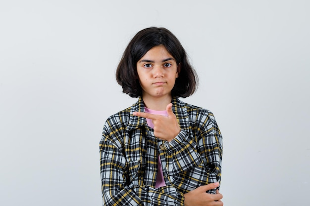 Preteen dziewczyna w koszuli, kurtce wskazującej na bok, widok z przodu.