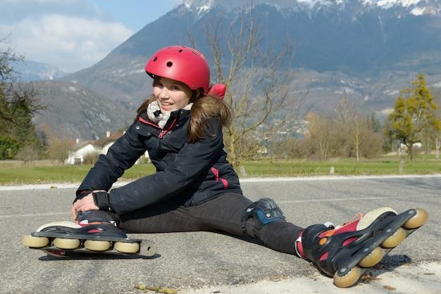 Preteen dziewczyna w rollerskate siedzi na drodze