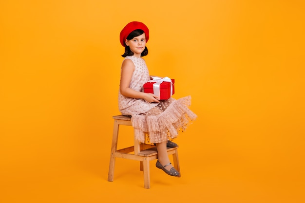 Preteen dziewczyna w sukni trzymając prezent urodzinowy. dzieciak z teraźniejszością siedzi na krześle na żółtej ścianie.