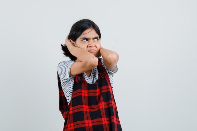 Preteen dziewczyna w t-shirt, kombinezon, ściskając głowę rękami