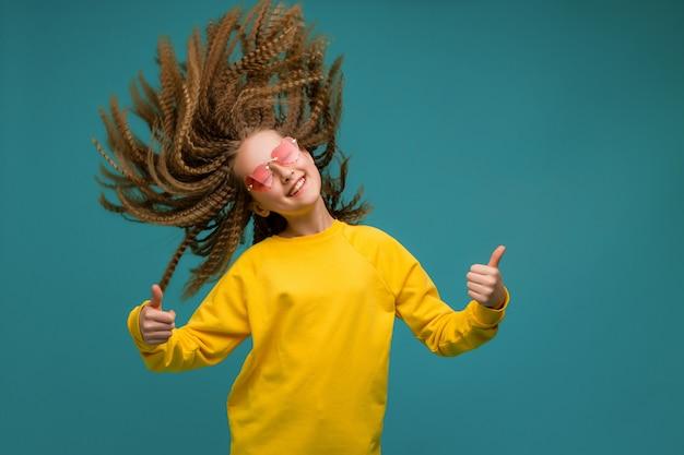 Preteen dziewczyna w żółtych ubrań ono uśmiecha się