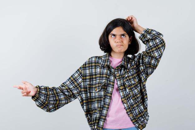 Preteen dziewczyna wskazując na bok podczas drapania się po głowie w koszuli, kurtce i patrząc zamyślony, widok z przodu.