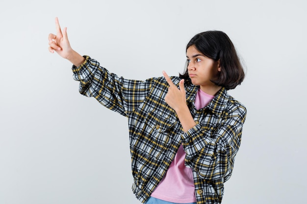 Preteen dziewczyna wskazując na bok w koszuli, widok z przodu kurtki.