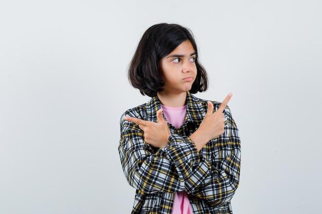 Preteen dziewczyna wskazując na różne strony w koszuli, kurtce, widok z przodu.