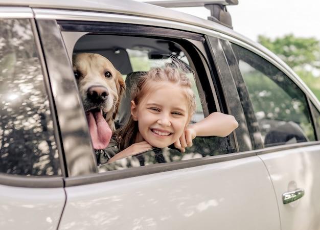 Preteen dziewczyna z golden retriever pies siedzi w samochodzie i patrząc przez okno otwarte i uśmiechnięte. dziecko dziecko z rasowym pieskiem w pojeździe na zewnątrz