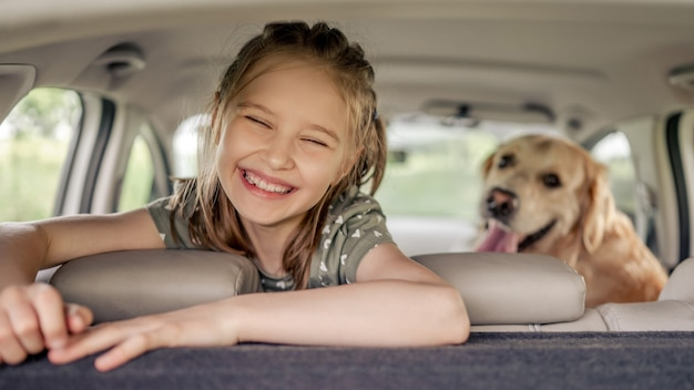 Preteen dziewczyna z golden retriever psem siedzi w samochodzie, patrząc w kamerę i uśmiechając się. dziecko dziecko z rasowym pieskiem w samochodzie w środku