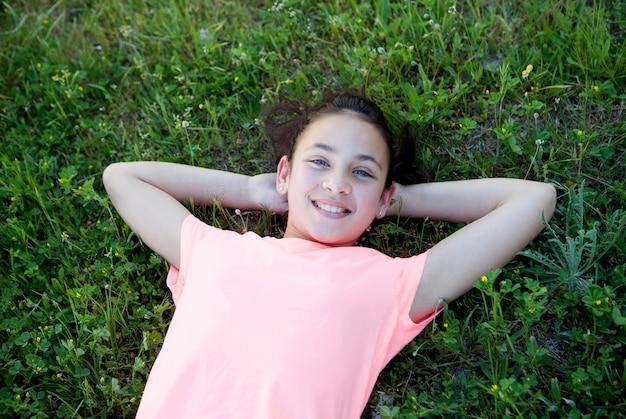 Preteen dziewczyna z niebieskimi oczami kłama na trawie