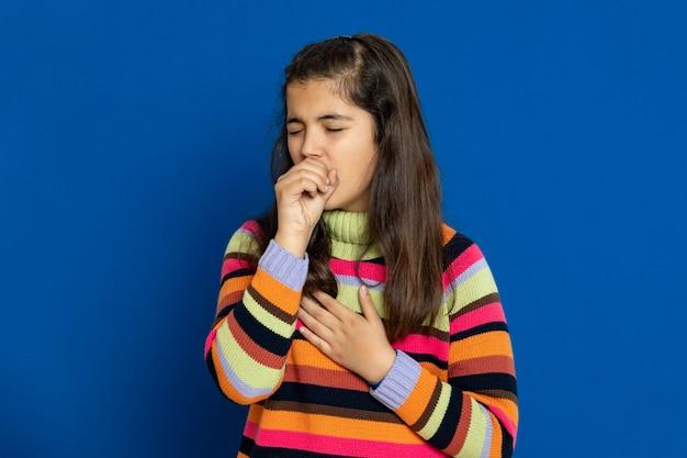Preteen dziewczyna z pasiastym dżersejem gestykuluje nad niebieską ścianą