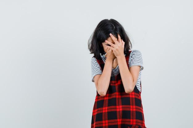 Preteen dziewczyna zakrywająca twarz rękami w t-shirt