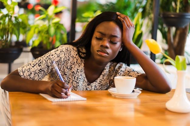 Pretty african-american kobieta siedzi przy stole w pobliżu laptopa i patrząc z wyrazem zmęczonej twarzy.