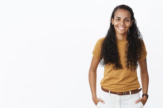 Pretty african american studentka patrząc na kamery z zadowolonym uśmiechem