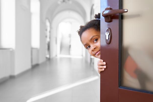 Pretty african girl ukrywanie z otwartych drzwi w szkolnym korytarzu, patrząc na kamery.