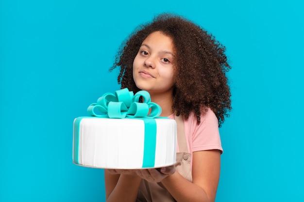 Pretty afro kobieta z tortem urodzinowym. koncepcja piekarni