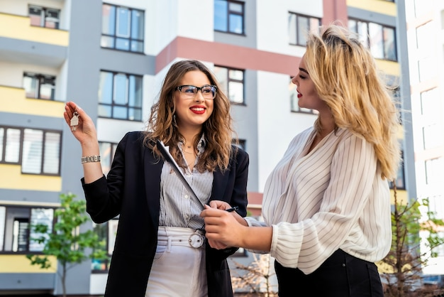 Pretty agent nieruchomości omawiający nieruchomości z klientką na świeżym powietrzu w pobliżu nowego domu. koncepcja sle