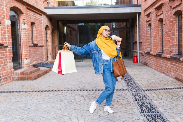 Pretty arabska kobieta z torby na zakupy po centrum handlowym