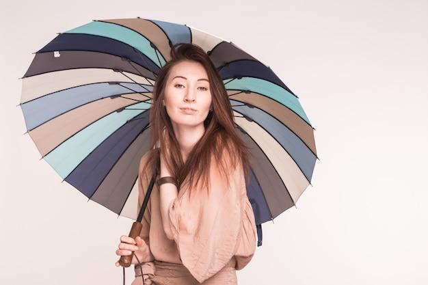 Pretty asian kobieta trzyma kolorowy parasol na białej powierzchni