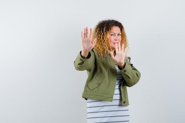 Pretty blond kobieta pokazując gest stopu w zielonej kurtce i patrząc zniesmaczony, widok z przodu.