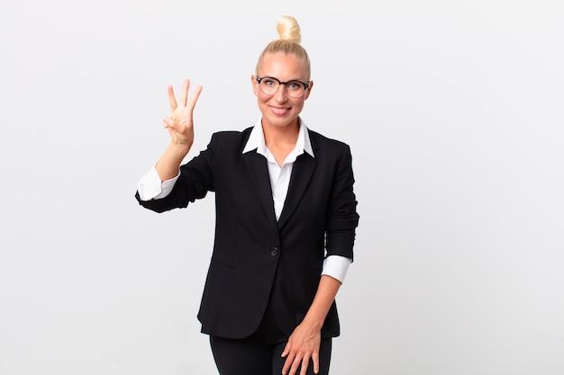 Pretty blond kobieta uśmiecha się i wygląda przyjaźnie, pokazując numer trzy. pomysł na biznes