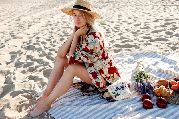 Pretty blond kobieta w słomkowym kapeluszu siedzi na tropikalnej plaży, ciesząc się wakacjami w pobliżu oceanu.