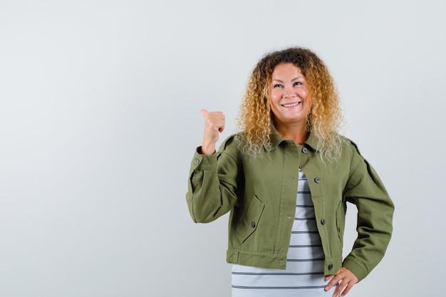 Pretty blond kobieta w zielonej kurtce, wskazując kciukiem z powrotem i patrząc wesoło, widok z przodu.