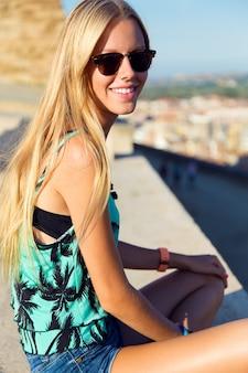 Pretty blondynka siedzi na dachu.