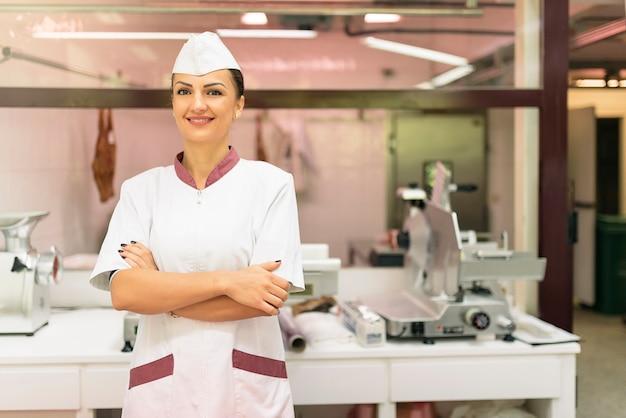 Pretty butchery kobieta pracująca w sklepie mięsnym.