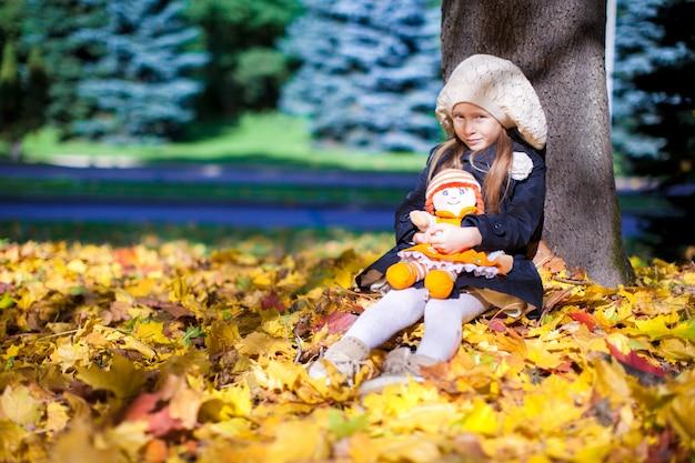 Pretty fashion girl siedzi pod drzewem klonowym z lalką w słoneczny jesienny dzień