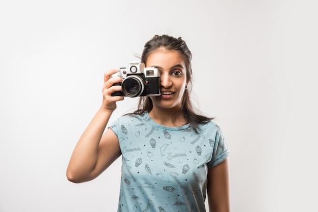 Pretty indian azjatyckich dziewczyna z retro camera, stojąc na białym tle nad białym tłem. trzymanie lub klikanie zdjęć