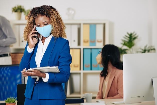 Pretty kręcone młody czarny bizneswoman w masce medycznej czytanie dokumentu w schowku podczas nawiązywania połączenia telefonicznego