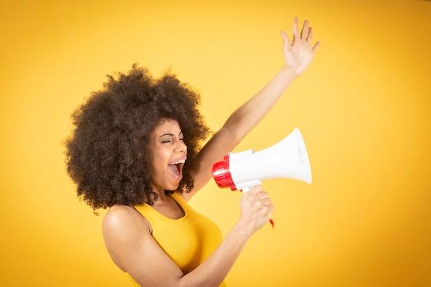 Pretty młoda kobieta afroamerykanów uśmiechnięta z kręconymi włosami i wrzeszczy z czerwonym megafonem.