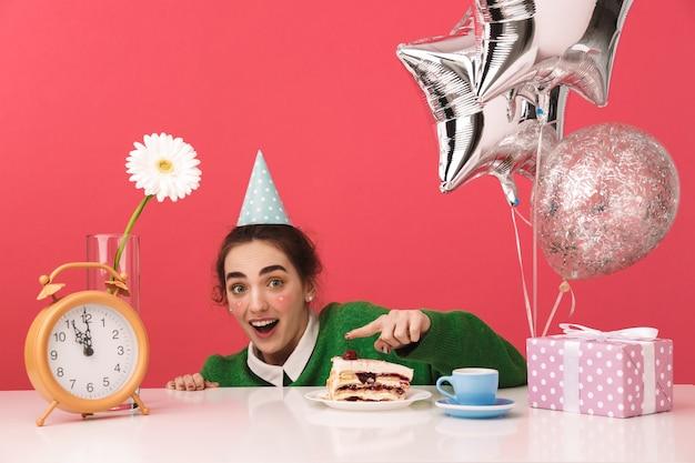 Pretty nerd dziewczyna siedzi przy stole na białym tle, obchodzi swoje urodziny tortem