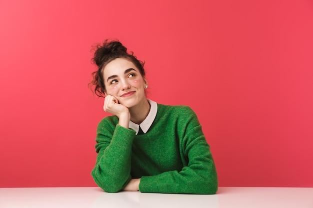 Pretty nerd dziewczyna siedzi przy stole na białym tle