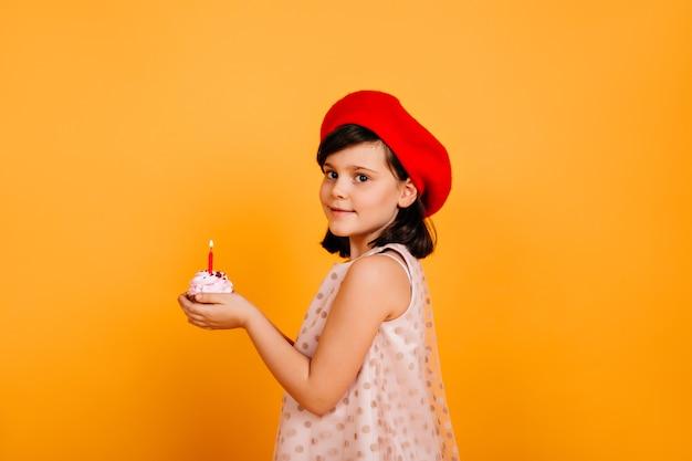 Pretty preteen dziewczyna trzyma tort ze świecą. stylowe dziecko obchodzi urodziny.
