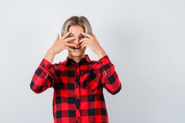 Pretty teen boy patrząc przez palce w kraciastej koszuli i patrząc zdziwiony, widok z przodu.