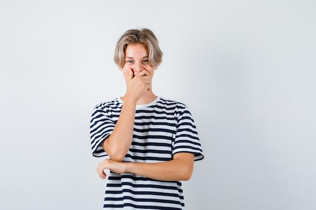 Pretty teen boy w paski t-shirt z ręką na ustach i patrząc szczęśliwy, widok z przodu.