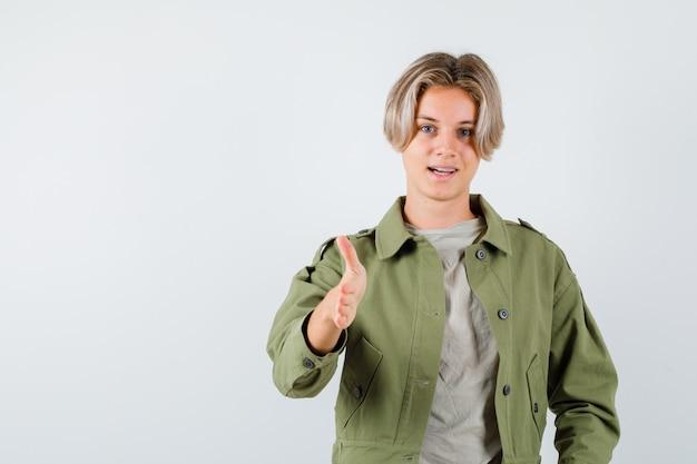 Pretty teen boy w zielonej kurtce, oferując uścisk dłoni jako powitanie i patrząc pewnie, widok z przodu.