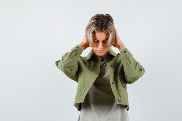 Pretty teen boy w zielonej kurtce, trzymając ręce na uszach i patrząc w trudnej sytuacji, widok z przodu.