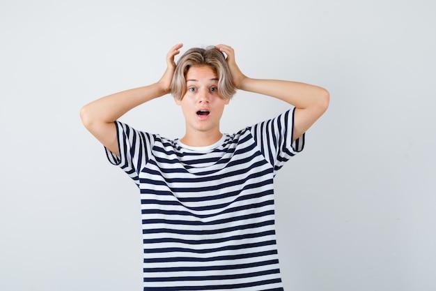 Pretty teen chłopiec z rękami na głowie w paski t-shirt i patrząc w szoku, widok z przodu.