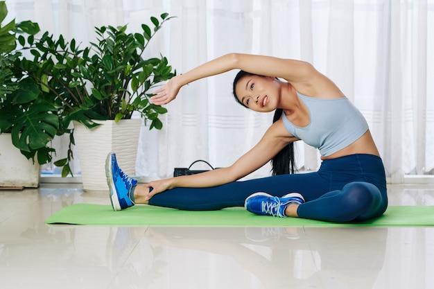 Pretty uśmiechnięta młoda chinka siedzi na macie do jogi w domu i robi boczne zakręty