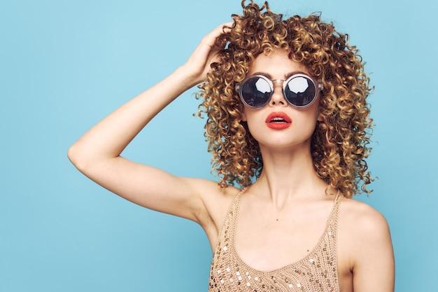 Pretty woman czerwone usta kręcone włosy ręka na głowie okulary przeciwsłoneczne styl życia niebieskie tło