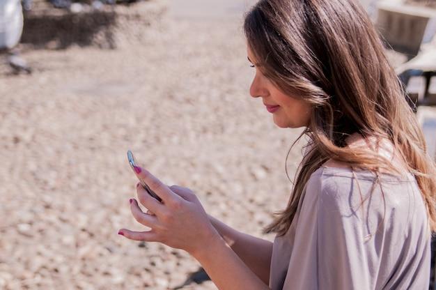 Pretty woman przy użyciu jej telefonu komórkowego, siedząc na drewnianej ławce. styl casual - dżinsy i koszula. happy młoda kobieta przy użyciu smartphone w słoneczny dzień