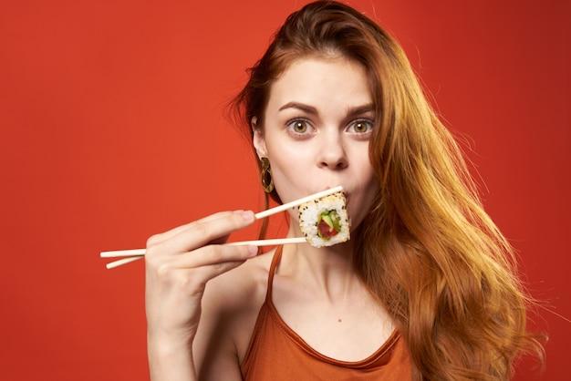 Pretty woman rudowłosy kobieta pałeczki do sushi dieta żywności czerwony.