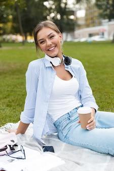 Pretty woman w parku na zewn?trz przy u?yciu komputera laptop s?uchania muzyki picia kawy.