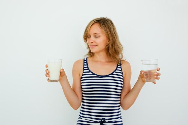 Pretty woman wybierając między wody i mleko