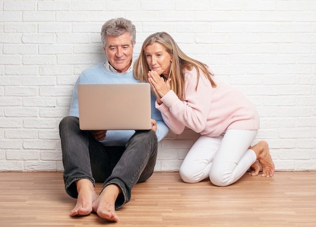 Pretty wyższych para siedzi na podłodze ich domu z komputera przenośnego