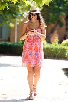 Pretty young girl texting na telefon komórkowy w ogrodzie.